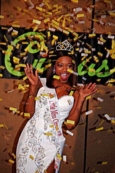 The pagent winner is showered with confetti from a handheld confetti cannon.